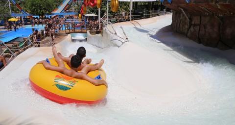 toboágua com duas pessoas descendo em uma bóia dupla amarela