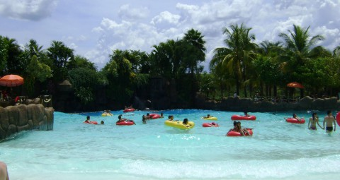 piscina de ondas com muitas pessoas em cima de bóias, água