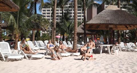 pessoas ao sol na praia artificial com quiosques areia