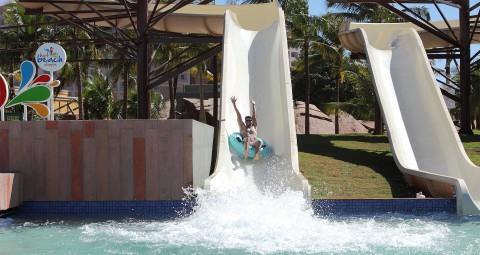 Homem descendo toboágua com as mão para o alto Hot Beach
